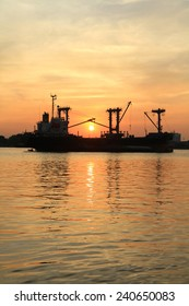 Silhouette of cargo ship in the river on twilight time