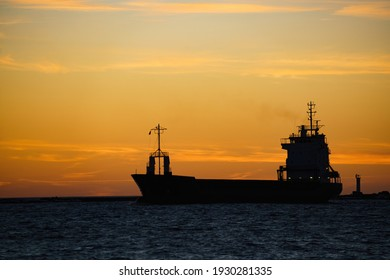 a silhouette of a cargo ship at sunset.