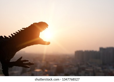 silhouette of Carnotaurus and buildings in sunset time