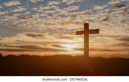 Silhouette of catholic cross at sunset background.