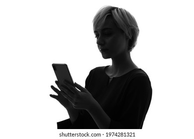 Silhouette of caucasian woman using a smart phone.