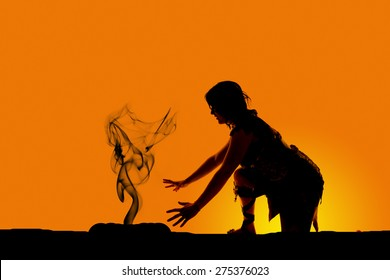 A silhouette of a cave woman kneeling down by a fire.