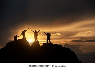 Silhouette of celebrating life, Hikers climbing up mountain cliff. Climbing group helping each other while climbing up in sunset. Concept of help and teamwork, Limits of life and Hiking su