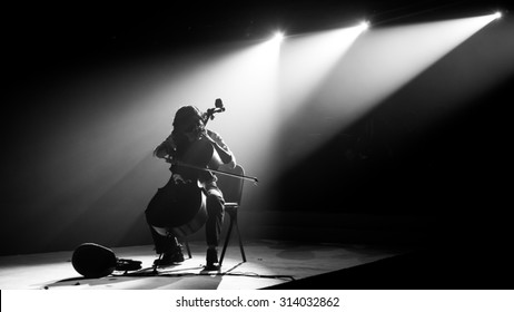 Silhouette cello player perform on stage with spotlight in monochrome,noise added