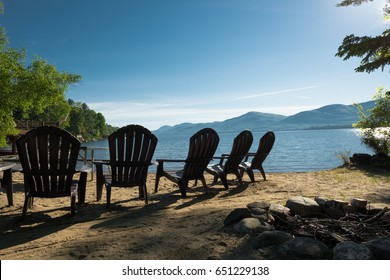 Silhouette of chairs on a lake side sandy beach on a beautiful quiet and calm early summer blue sky morning,