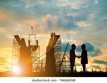 Silhouette Chief Engineer of two companies Shake hands in a big event. over blurred background sunset pastel for industry background with Light fair