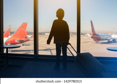 Silhouette of child boy with backpack looking at plane and waiting for boarding in the airport.