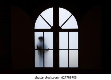 A silhouette of a child near a window inside a building