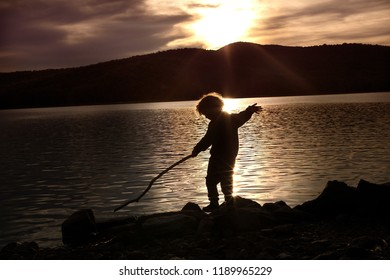 A silhouette of a child playing with a stick at the lake during sunset in Vermont. The sun is setting behind the mountains. The shadow of the child shows he is holding a large stick, standing on rocks