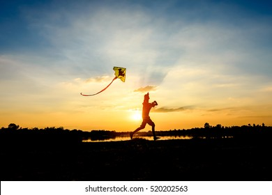 silhouette of children flying a kite at sunset invoke childhood memories