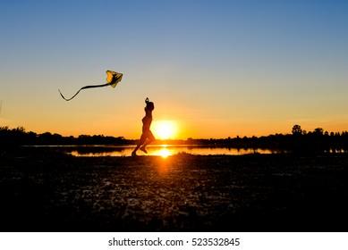 silhouette of children flying a kite at sunset invoke childhood memories