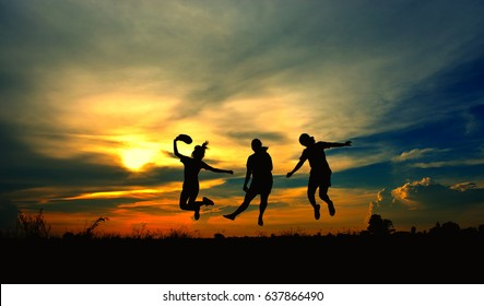 Silhouette of a children jumping on sky light of the sunset, look like they can flying.