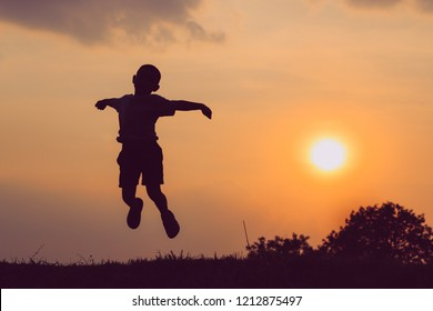 Silhouette of children jumping at sunset. Lifestyle freedom concept.