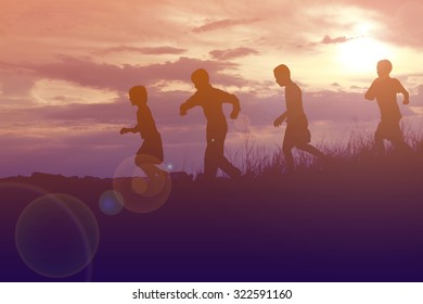 silhouette children playing happy time at sunset