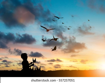 Silhouette Children playing paper birds that fly with real birds freely over blurred natural. Imagination is more important to the development of children's brains. Learning and freedom concept.