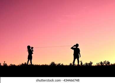 Silhouette of children playing string phone at the sky sunset