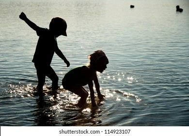 Silhouette of children playing in water