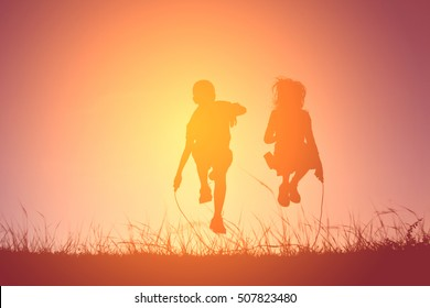Silhouette children rope jumping on the sky sunset. Time on holiday happy and fun , vintage tone