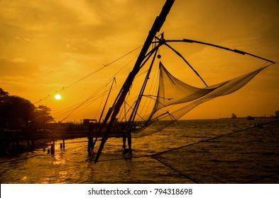 Silhouette of Chinese fishing net in Fort Kochi beach at sunset.