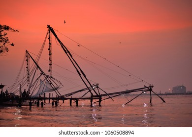 Silhouette of chinese fishing nets in fort kochi during sunset.