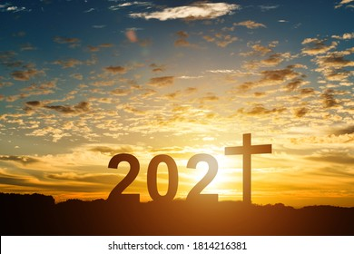 Silhouette of Christian cross with 2021 years at sunset background.