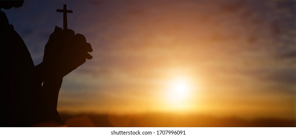 Silhouette of christian holding cross in hands to praying for blessing from god at sunset background.