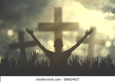 Silhouette of christian prayers raising hand while praying to the Jesus
