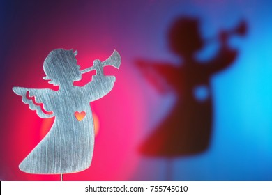 Silhouette of Christmas angel playing the trumpet in the bright rays of red and blue color