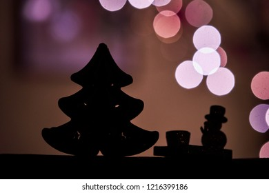 Silhouette of Christmas tree and snowman and in the background christmas lights bokeh