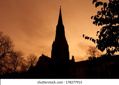 Silhouette of church dome in Berlin backlit by sunset colors