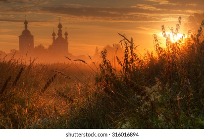 Silhouette of church in morning fog at sunrise