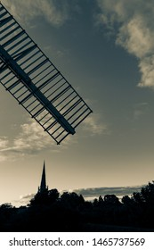 Silhouette of church spire and windmill sail