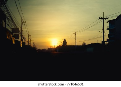 Silhouette of city and sunrise ,electric pole,motorcycle,home,street.