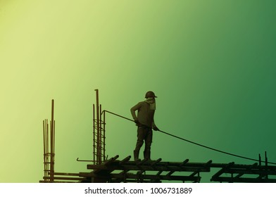 Silhouette City worker, construction crews to work on high ground heavy industry and safety concept over blurred natural background sunset pastel