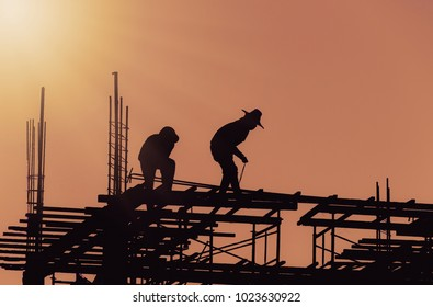 Silhouette City worker, construction crews to work on high ground heavy industry and safety concept over blurred natural background sunset
