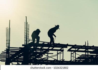 Silhouette City-Mitarbeiter, Bauspersonal für Arbeiten in der HochbodenSchwerindustrie und Sicherheitskonzept auf unscharfem Naturhintergrund Sonnenuntergang