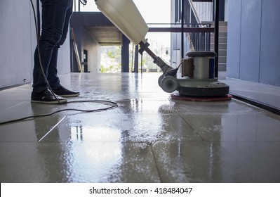 Silhouette cleaning floor with machine.