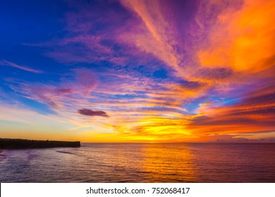 Silhouette of a cliff against the background of an colorful sunset. Sea waves break on the rocks. Sunset on Jimbaran, South Kuta, Bali, Indonesia.
