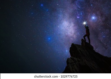 Silhouette of climber or backpacker. Light holds up over his head. Standing on rocky mountain peak and Milky Way Galaxy, success or winner, leader concept. High iso with Noise.