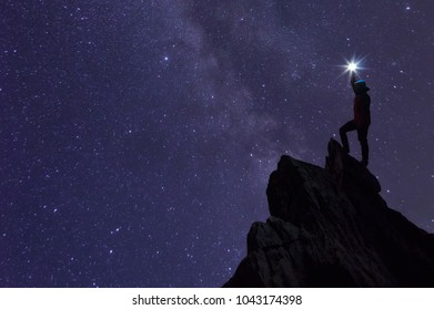 Silhouette climber or backpacker, Light holds up over his head. Standing on rocky mountain peak against Milky way galaxy, stars and space dust in the universe, Success or winner, leader concept.