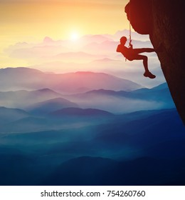 Silhouette of climber girl on a cliff against sunset in a mountain valley
