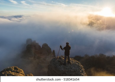 Silhouette of a climber high in the mountains above the clouds at sunset