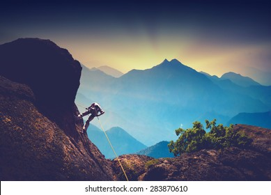 Silhouette of climber on a cliff against beautiful sunset in a high mountains