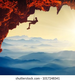 Silhouette of climber on a cliff over the foggy mountain valley in a light of sunrise. Extreme sports.
