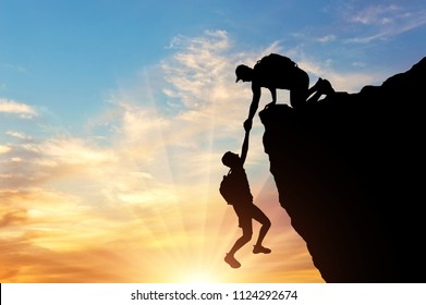 Silhouette of a climber saves another climber pulling him from the abyss. Conceptual Scene