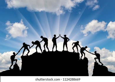 Silhouette of climbers who climbed to the top of the mountain thanks to mutual assistance. Conceptual scene of alpinists and teamwork