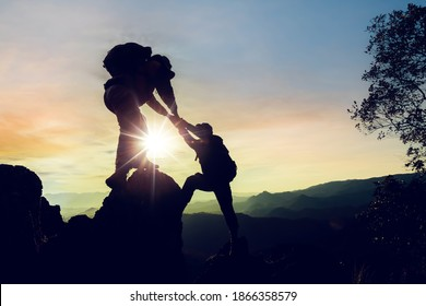 Silhouette climbing buddies help each other climb up the mountain at sunrise as the right lifestyle idea