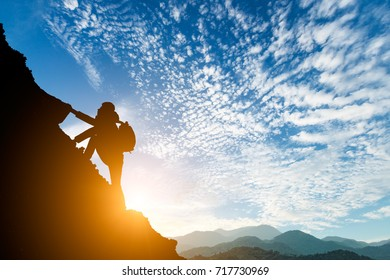 silhouette of climbing man in mountains concept of sports at beautiful sunset