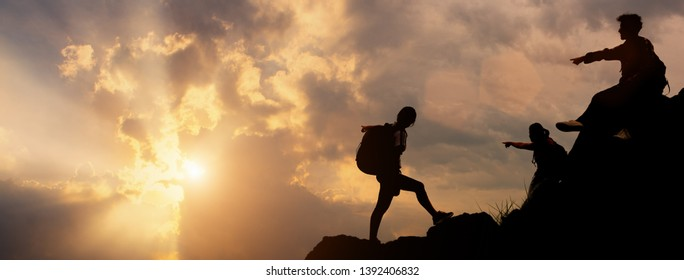 Silhouette of the climbing team pointing sky with god of sunlight in beautiful time of natural. Concept of the reward of a successful person.