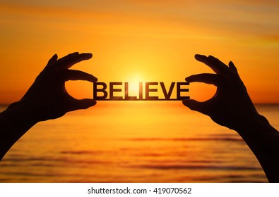 Silhouette, Close up Hand holding BELIEVE text with blurred sea sunset. sunlight effect.